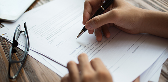 Main qui signe un document administratif